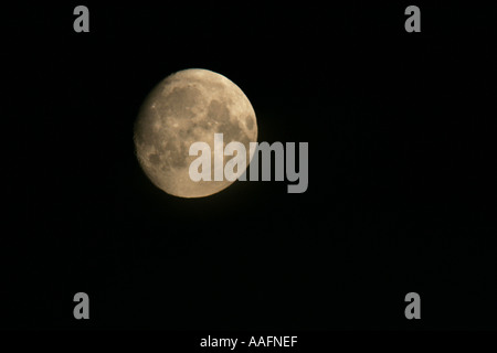 Almost full moon over Belfast Northern Ireland tinted by atmospheric pollution - Stock Photo