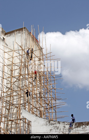 Building under construction with workers on Eucalyptus tree pole scaffolding in Addis Ababa Ethiopia Africa - Stock Photo