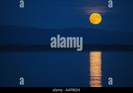 Full moon rising over the Discovery Islands and the Coastal Mountains. - Stock Photo