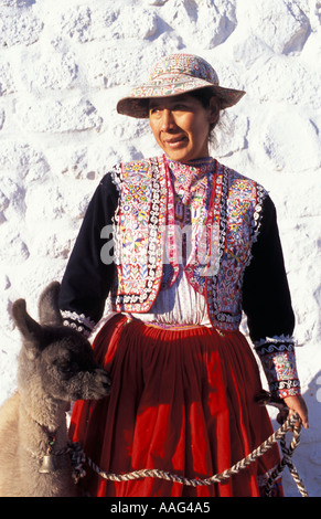 A Quechua woman from the Colca Valley in distinctive local costume with a 12 day old llama Nr Chivay Colca Canyon - Stock Photo