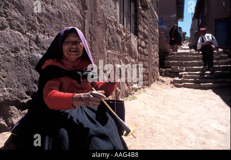Woman from Taquile spinning wool outside a shop on Taquile s plaza Wearing distinctive costume Taquile Lake Titicaca - Stock Photo