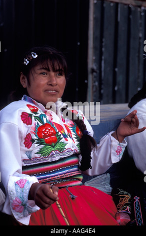 Woman from Amantani spinning wool Wearing embroidered village specific costume Amantani Lake Titicaca Peru - Stock Photo
