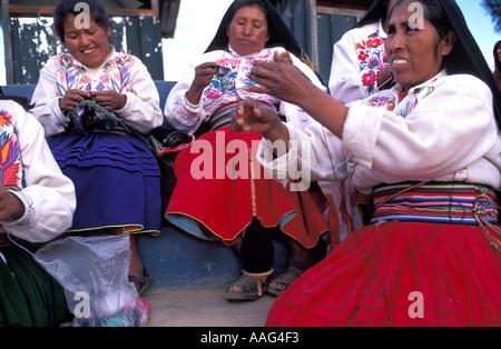 Group of friendly women from Amantani spinning wool knitting Wearing island specific costume Amantani Lake Titicaca - Stock Photo