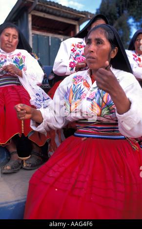 Friendly women from Amantani in distinctive tribal costume spinning wool Amantani island Lake Titicaca Peru South - Stock Photo