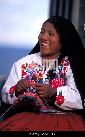 Friendly woman from Amantani in distinctive tribal costume knitting a woollen cap Amantani island Lake Titicaca - Stock Photo
