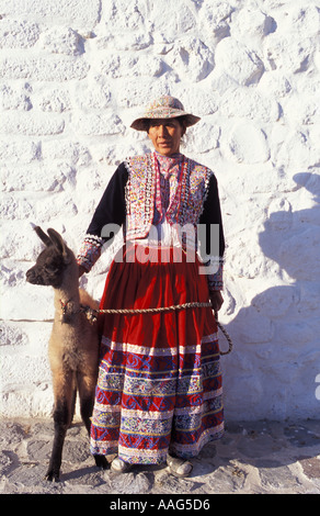 Quechua woman with 12 day old llama in tribal costume at Maca village near Chivay Colca Canyon Peru South America - Stock Photo