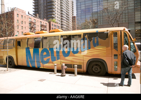 People wait to enter a Metrocard bus in a street in New York City USA April 2006 - Stock Photo