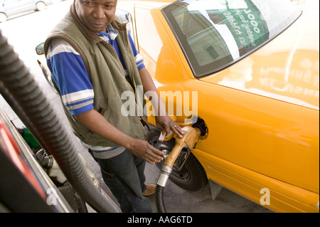 Filling up a yellow cab at a gas station in Harlem New York City USA April 2006 - Stock Photo
