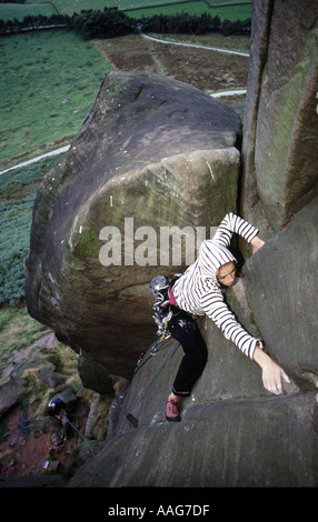 A female rock climber ascends a climb at the roaches in Staffordshire, nr Leek, Peak District National Park, England - Stock Photo