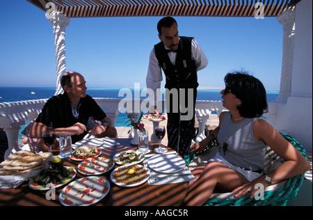 Waiter serving meal Felfella Egyptian restaurant Hurghada Eqypt - Stock Photo