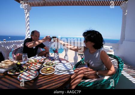 Couple toasting with red wine Felfella Egyptian restaurant Hurghada Eqypt - Stock Photo