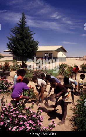 Topnaar schoolchildren working in their school garden at the heart of the Namib Desert - Stock Photo