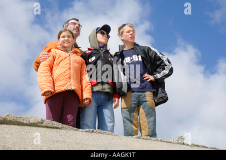 a father and his children enjoying the view from the top of an old bunker at the beach of Blavand in Denmark - Stock Photo