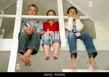 three kids sitting on a landing in a summer cottage in Denmark with their bare feet dangling down - Stock Photo