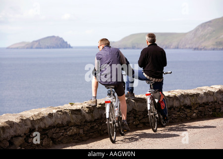 Ireland Kerry Dingle Peninsula Slea Head cyclists on coastal road looking to Dunmore Head - Stock Photo