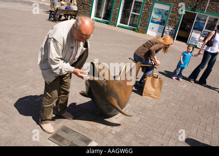 Ireland Kerry Dingle seafront man touching bronze sculpture of Fungie the Dingle dolphin sculpted by James Bottoms - Stock Photo