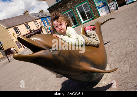 Ireland Kerry Dingle seafront girl riding bronze sculpture of Fungie the Dingle dolphin - Stock Photo