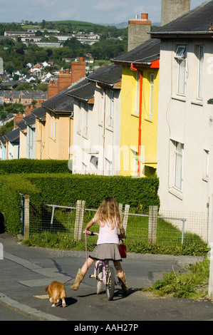 young girl cycling taking dog for walk, on a local authority council estate houses Penparcau Aberystwyth Ceredigion - Stock Photo