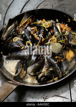 Mussels being prepared with vegetables and seasoning in a saucepan on a professional cooker - Stock Photo