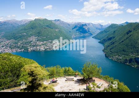 view from Monte San Salvatore 912 m over Lake Lugano and Lugano people resting on benches Lugano Ticino Switzerland - Stock Photo