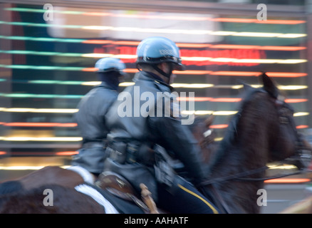 Mounted police officers in motion in Times Square, New York City - Stock Photo