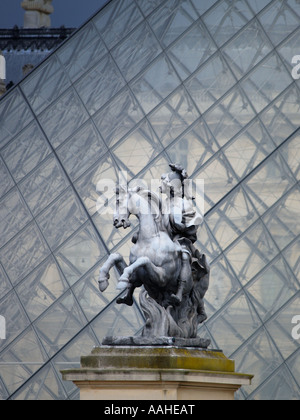 Statue sculpture of a soldier riding a prancing horse in front of the Louvre pyramid Paris France - Stock Photo