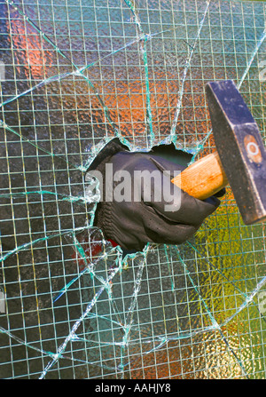 Burglar breaking and entering into a private property by smashing through wire enforced glass pane using a hammer. - Stock Photo