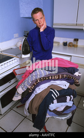 fedup man looking unhappy at giant mound of ironing waiting to be ironed on ironing board in kitchen of house - Stock Photo