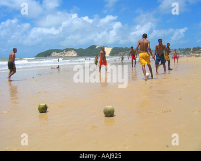 Young boys playing soccer on Praia do Ponta Negra beach in Natal Brazil using coconuts as goal posts - Stock Photo