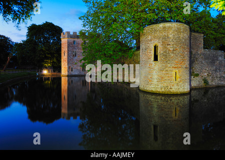 The moat and outer wall around the Bishop's Palace and gardens in the city of Wells at dusk. Somerset, England. - Stock Photo
