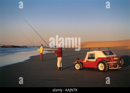 Two anlgers Rod Fishing at Kaizer Beach near East London Eastern Cape South Africa A red beach buggy car is parked close by Stock Photo