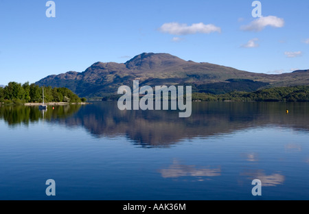Ben Lomond and its reflection in Loch Lomond as seen from Luss Pier - Stock Photo