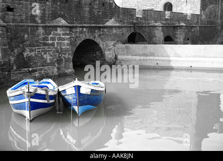 Black and white harbour with two blue boats Essaouria Morocco - Stock Photo