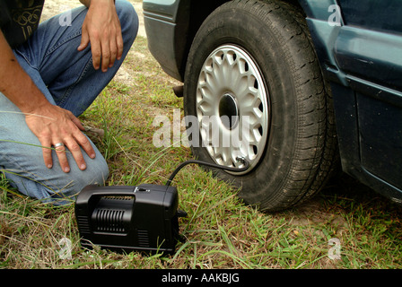 Tire Change inflating a flat tire - Stock Photo