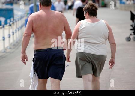An overweight couple walking along the promenade at Weymouth UK - Stock Photo