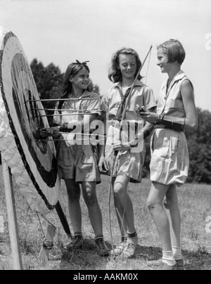 1930s 1940s THREE TEEN GIRLS STANDING BY ARCHERY TARGET BOWS ARROWS - Stock Photo