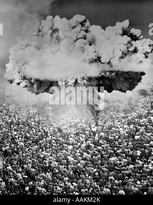 1950s 1960s ATOMIC BOMB SYMBOLIC MONTAGE MUSHROOM CLOUD OVER A VERY LARGE CROWD OF PEOPLE FACING THE EXPLOSION - Stock Photo