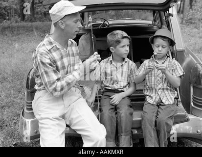 1950s 1960s FATHER TWO YOUNG SONS WITH FISHING RODS BY CAR OUTDOOR - Stock Photo