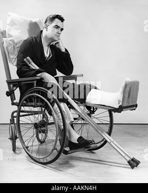 1940s MAN IN WHEELCHAIR WITH CAST ON LEFT LEG HOLDING CRUTCHES - Stock Photo