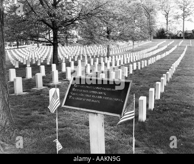 NATIONAL CEMETERY IN PHILADELPHIA WITH COMMEMORATIVE PLAQUE & AMERICAN FLAGS IN FOREGROUND - Stock Photo