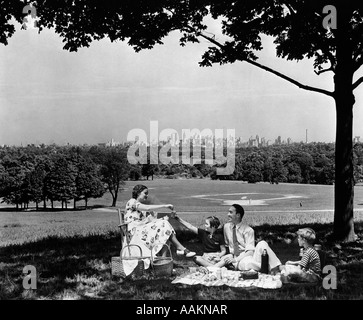 1930s 1940s FAMILY PICNICKING UNDER A TREE IN FAIRMONT PARK WITH SKYLINE OF PHILADELPHIA PA ON HORIZON - Stock Photo