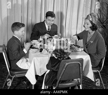 1960s SMILING HAPPY FAMILY OF FOUR EATING MEAL IN RESTAURANT MOM WEARING TURBAN STYLE HAT ADDRESSING HER DAUGHTER - Stock Photo