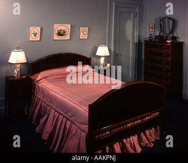 1930s 1940s BEDROOM DOUBLE BED WITH PINK SATIN BEDSPREAD - Stock Photo
