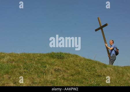 A man carries a wooden cross at a open- air Easter Friday service in Somerset. - Stock Photo