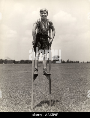 1930s 1940s SMILING HAPPY BOY WEARING STRIPED SHIRT & SHORT PANTS WALKING ON PAIR OF STILTS LOOKING AT CAMERA - Stock Photo