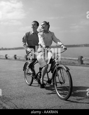 1950s SMILING HAPPY COUPLE MAN WOMAN RIDING TANDEM BICYCLE BUILT FOR TWO - Stock Photo