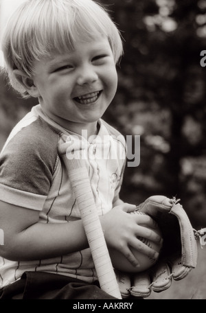 1980s YOUNG LAUGHING BLOND BOY WITH BASEBALL GLOVE & BAT SMILING LOOKING AT CAMERA - Stock Photo