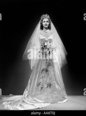 1940s FULL LENGTH PORTRAIT OF BRIDE IN WEDDING DRESS LOOKING AT CAMERA - Stock Photo
