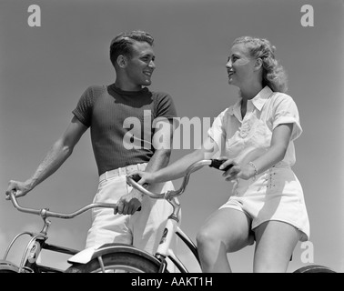 1930s 1940s SMILING BLONDE COUPLE ON BIKES LOOKING AT ONE ANOTHER - Stock Photo