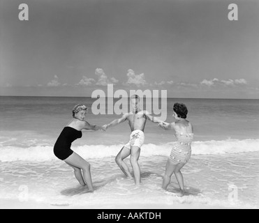 1950s MAN AND TWO WOMEN FROLICKING IN BEACH SURF - Stock Photo